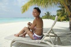 Ragazza su una chaise-lounge del sole sotto una palma in Maldive Fotografia Stock