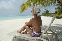Ragazza su una chaise-lounge del sole sotto una palma nella spiaggia delle Maldive Fotografie Stock