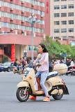 Ragazza su una e-bici nel centro urbano, Kunming, Cina Fotografia Stock