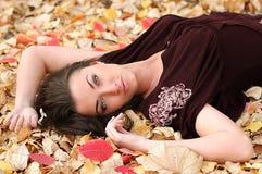 Ragazza su una moquette dai fogli Fotografia Stock