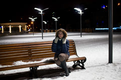 Ragazza su una notte di inverno che si siede su un banco Fotografia Stock
