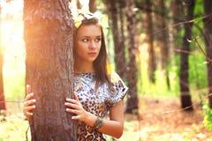 Ragazza su una priorità bassa degli alberi Fotografia Stock