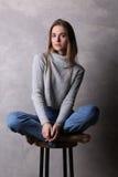 Ragazza su una sedia della barra con le gambe attraversate Fondo grigio Fotografie Stock