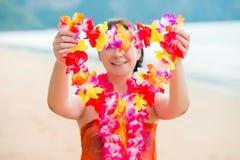 Ragazza sugli ospiti di benvenuti della spiaggia con Lei floreale ha tradizionale Fotografia Stock Libera da Diritti