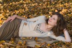 Ragazza sui fogli di autunno Fotografia Stock Libera da Diritti