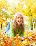 Ragazza sui fogli di autunno Fotografia Stock