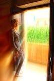 Ragazza sul balcone della casa nei raggi dorati Immagini Stock