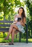 Ragazza sul banco in parco con ereader Fotografia Stock Libera da Diritti