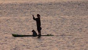 Ragazza sul bordo di pagaia a tempo di tramonto Fotografie Stock
