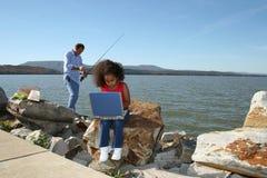 Ragazza sul calcolatore e sulla pesca Fotografia Stock Libera da Diritti