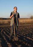 Ragazza sul lavoro di campo la terra al tramonto Immagine Stock
