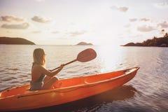 Ragazza sul mare del kajak al tramonto, progettazione sana di stile di vita Sport, sport acquatico di estate di ricreazione fotografia stock libera da diritti