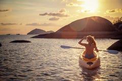 Ragazza sul mare del kajak al tramonto, progettazione sana di stile di vita Sport, sport acquatico di estate di ricreazione immagini stock