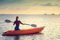Ragazza sul mare del kajak al tramonto, progettazione sana di stile di vita Sport, sport acquatico di estate di ricreazione fotografia stock