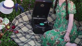 Ragazza sul picnic nel prato che ascolta l'annotazione sul grammofono d'annata stock footage