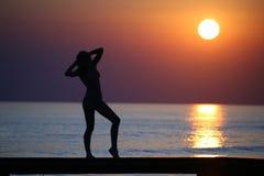 Ragazza sul ponticello contro il tramonto. Fotografie Stock