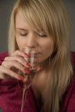 Ragazza sul sofà in studio con vetro di champagne Fotografie Stock Libere da Diritti