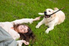 Ragazza sull'erba e giochi con il cane Fotografia Stock