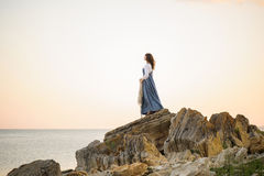 Ragazza sull'orlo di una scogliera che guarda fuori al mare fotografia stock