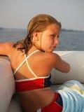 Ragazza sulla barca al tramonto Fotografie Stock