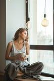 Ragazza sulla finestra con una tazza di caffè e una rivista fotografie stock libere da diritti
