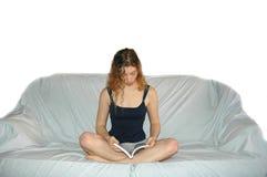 Ragazza sulla lettura del sofà Fotografie Stock Libere da Diritti