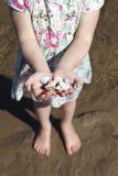 Ragazza sulla manciata della holding della spiaggia di Seashells Fotografia Stock