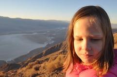 Ragazza sulla montagna che guarda giù Fotografia Stock