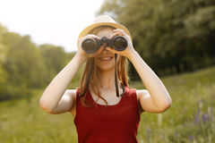 Ragazza sulla natura con il cappello e binoculare Estate fotografie stock