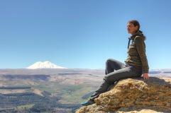 Ragazza sulla roccia, su un fondo di nonte Elbrus Fotografie Stock Libere da Diritti