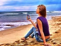 Ragazza sulla sabbia vicino ad aiuto di chiamata del mare dal telefono Immagini Stock