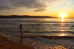 ragazza sulla spiaggia, alba immagine stock