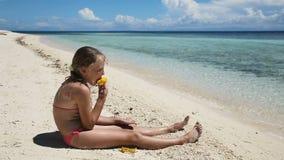 Ragazza sulla spiaggia che mangia la frutta del mango archivi video