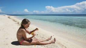 Ragazza sulla spiaggia che mangia la frutta del mango stock footage