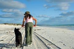 Ragazza sulla spiaggia con il cane fotografie stock libere da diritti