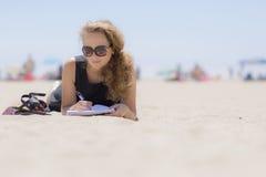 Ragazza sulla spiaggia con un taccuino Immagini Stock Libere da Diritti