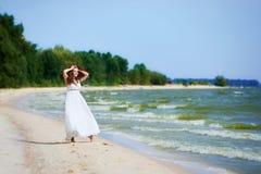 Ragazza sulla spiaggia in un vestito bianco immagini stock