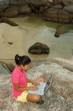 Ragazza sulla vacanza per mezzo del computer portatile all'esterno Fotografia Stock