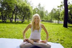 Ragazza sveglia allegra bionda che fa yoga in parco che sorride nel moto, concetto della gente di stile di vita Fotografia Stock
