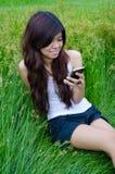 Ragazza sveglia asiatica che texting sul prato Fotografia Stock Libera da Diritti
