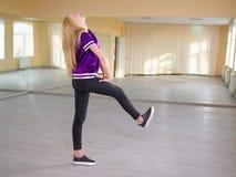Ragazza sveglia, biondo, ballando, mettendo il suo piede in avanti, posando in uno studio leggero di ballo Fotografie Stock Libere da Diritti