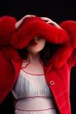 Ragazza sveglia in cappotto di pelliccia rosso fotografia stock