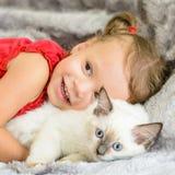 Ragazza sveglia che abbraccia gattino Fotografia Stock