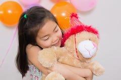 Ragazza sveglia che abbraccia giocattolo molle ad una festa di compleanno Fotografia Stock