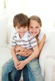 Ragazza sveglia che abbraccia il suo piccolo fratello Fotografia Stock