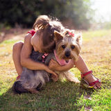 Ragazza sveglia che abbraccia un piccolo cane Fotografia Stock Libera da Diritti