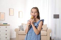 Ragazza sveglia che canta in microfono immagine stock