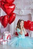 Ragazza sveglia che celebra insieme giorno di nascita vicino ai palloni rossi Scena adorabile della ragazza in vestito blu Immagine Stock