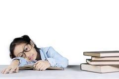 Ragazza sveglia che dorme con un mucchio dei libri Fotografia Stock