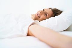 Ragazza sveglia che dorme a letto svegliando allungamento e sorridere Immagine Stock